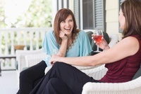 Two Women Drinking Wine on Porch