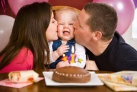 Parents Kissing Girl at First Birthday Party