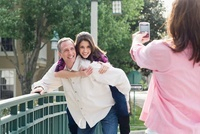 Woman Taking Photograph of Man Giving Daughter Piggyback Rid