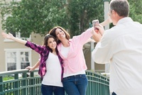 Man Taking Photograph of Mother and Daughter