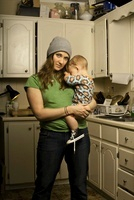 Mother Holding Son in Cluttered Kitchen