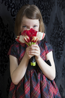 Young Girl Obscuring Face with Bouquet of Flowers