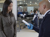 Security Guard Removing Prohibited Item from Woman's Bag at Airport