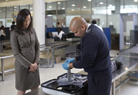 Security Guard Examining Contents of Suitcase in Airport