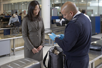 Security Guard Examining Contents of Woman's Bag at Airport