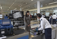 Security Guard Examining Contents of Woman's Suitcase in Airport