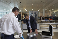 Businessman Opening Laptop for Security Guard in Airport
