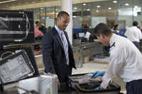 Security Guard Checking Businessman's Suitcase in Airport