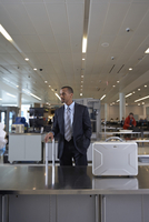 Businessman Waiting for Security Baggage Check in Airport
