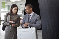 Business People Checking Time and Boarding Passes in Airport
