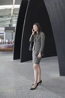 Businesswoman Talking on Cell Phone in Airport Terminal