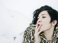 Woman Lying in Snow Smoking Cigarette