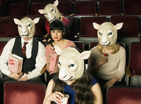 Group of People Wearing Sheep Masks in Movie Theatre