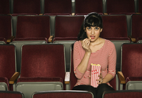 Woman Eating Popcorn and Watching Movie in Theatre