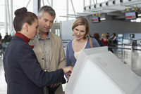 Employee Helping Couple Check In at Airport