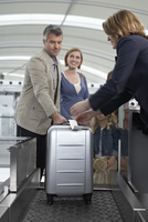 Family Checking Luggage at Airport