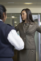 Businesswoman Being Scanned with Metal Detector at Airport