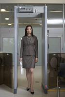 Businesswoman Walking Through Metal Detector in Airport