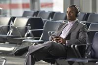 Businessman Wearing Headphones in Airport Waiting Area