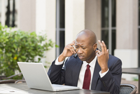 Stressed Businessman with Laptop and Cell Phone