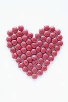 close-up of red pills arranged into heart shape on white background