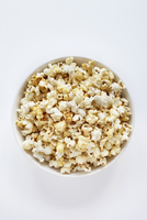 Popped popcorn in bowl on white background