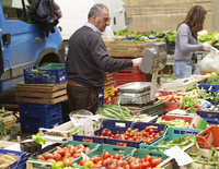 vendors sell vegetables at village farmers market, Cortona, Italy