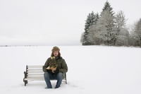 Man Holding Miniature Christmas Tree and Sitting on Bench in Snow Covered Field