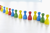 Multi-colored people-like playing pieces in a row on white background