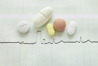 close-up of an electrocardiogram report and variety of pills