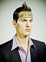 """male fashion model looking """"vacant"""" with a tin plate bolted to his head saying """"Not In Service"""""""