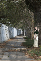 a young woman wearing formal clothing standing outside of a cemetery in New Orleans
