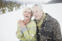 Selective focus portrait of couple laughing in the snow.