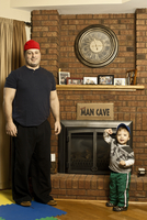 Father and Son Standing by Fireplace in Man Cave