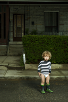 Boy Standing on Neighbourhood Street in Diaper and Rubber Boots