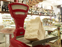 large wedge of parmesan cheese on red antique weigh scale in specialty meat and antipasto shop, Modena, Italy