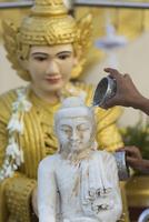 Washing of Buddha statue at Shwedagon Pagoda, Yangon, Myanmar