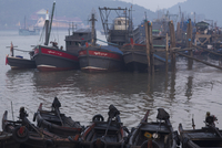 Fishing boats with reclining Buddha in morning light in the harbour city of Myeik in southern Myanmar