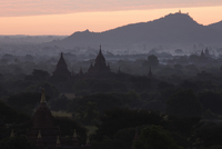 Temples at sunrise with mountains in background, Bagan, Myanmar