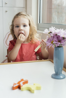 A young girl eating string cheese