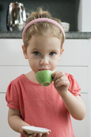 A young girl drinking from a teacup