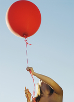 A teenaged girl holding a red balloon