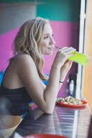 Teenage girl with plate of tacos and drinking soda at a Mexican restaurant in Portland, Oregon.
