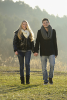 Young couple walking and holding hands in an autumn landscape, Bavaria, Germany