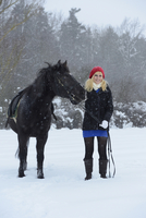 Young Woman with a black Arab-Haflinger horse standing on a snowy field in winter, Bavaria, Germany