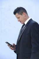 Close-up of a young businessman looking down at smartphone, Bavaria, Germany