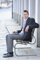 Young Businessman with Laptop Sitting on Bench, Bavaria, Germany