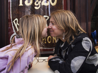 Mother and daughter nose-to-nose on terrace of french cafe, Paris, France