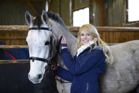 Young Woman grooms a Half Arabian Quarterhorse in his stable, Bavaria, Germany
