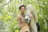 Portrait of young woman with icelandic horse standing under a flowering cherry tree in spring, Germany